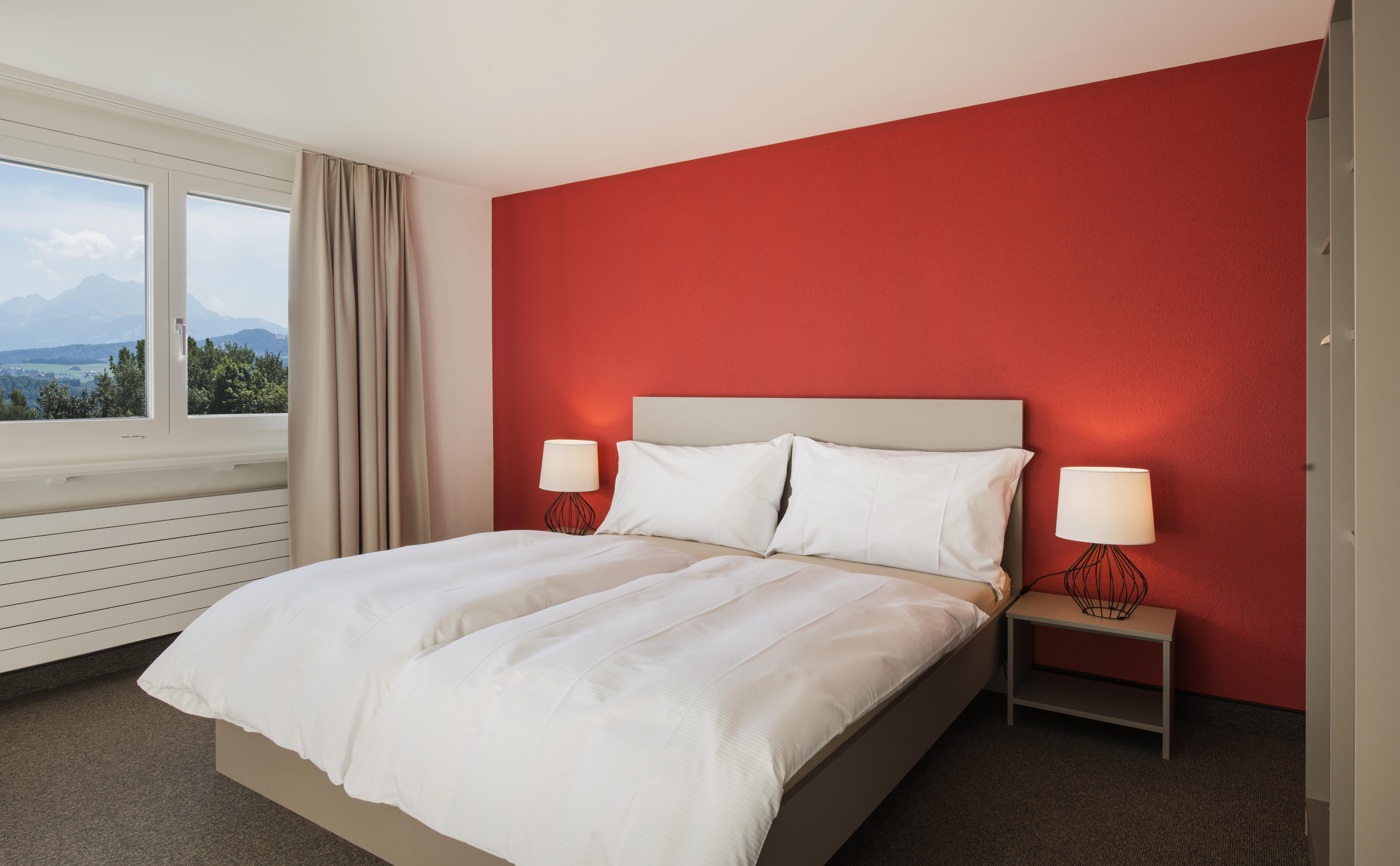 Chambre double avec mur rouge au Domaine-Notre-Dame de la Route