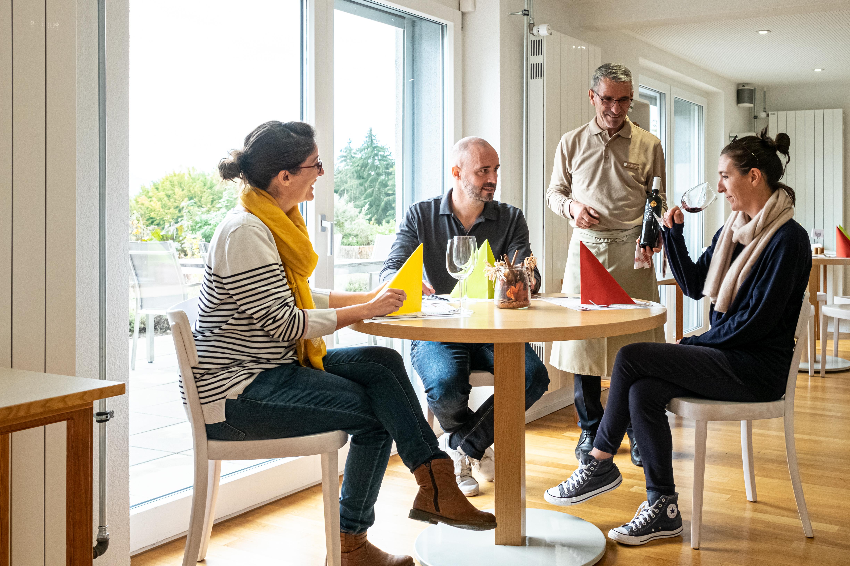 3 personnes à une table du Restaurant le Jardin dégustant du vin