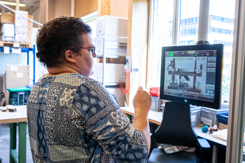 Femme regardant un écran de contrôle d'une machine